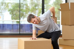 Man moving boxes suffering back ache